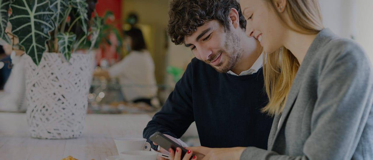 Imagen de una mujer y un hombre mirando un teléfono.